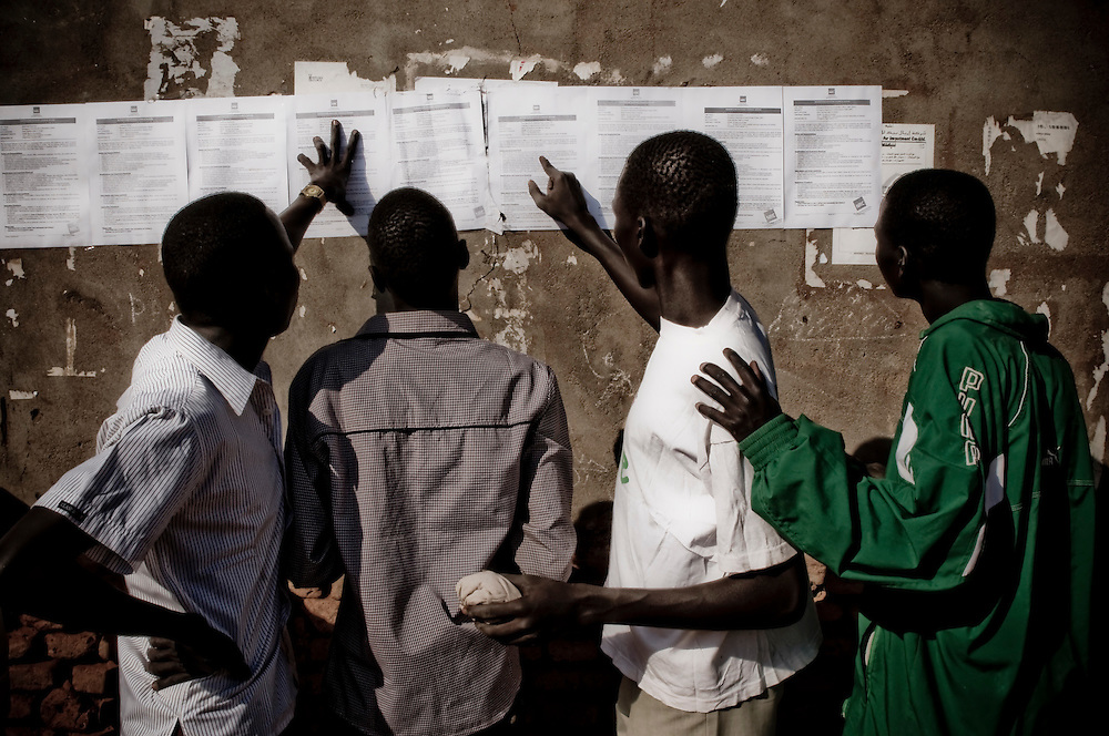Southern Sudanese refugees from the North look at job listings outside a church in the Southern Sudanese town of Aweil. Sudan recently voted on whether or not to remain with the North or to set out alone as the world's newest nation. (© William B. Plowman)