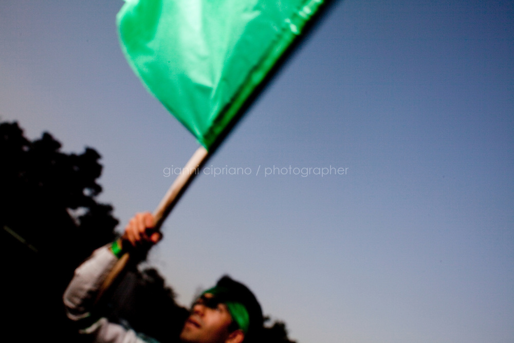 3 June, 2009. Tehran, Iran. A Supporter of reformist candidate Mir Hossein Moussavi waves a green flag gather at Tehran University to express its support to the candidate. Green is the color adopted by the supporters of candidate Moussavi in the elections of June 12th. On the other side of the street are supporters of Ahmadinejad. Conservative reformist candidate Mir Hossein Mousavi is running against the ultra-conservative current President of Iran Mahmoud Ahmadinejad. <br /> &copy;2009 Gianni Cipriano<br /> cell. +1 646 465 2168 (USA)<br /> cell. +39 328 567 7923<br /> gianni@giannicipriano.com<br /> www.giannicipriano.com