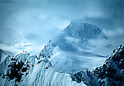 Three climbers sihouetted on a ridge of Mount Dickey in the Alaska Range near Mount McKinley.