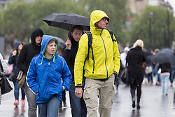 © Licensed to London News Pictures. 14/05/2015. London, UK. People cross Westminster Bridge during heavy rain and wet and windy weather in Westminster, central London today. Photo credit : Vickie Flores/LNP
