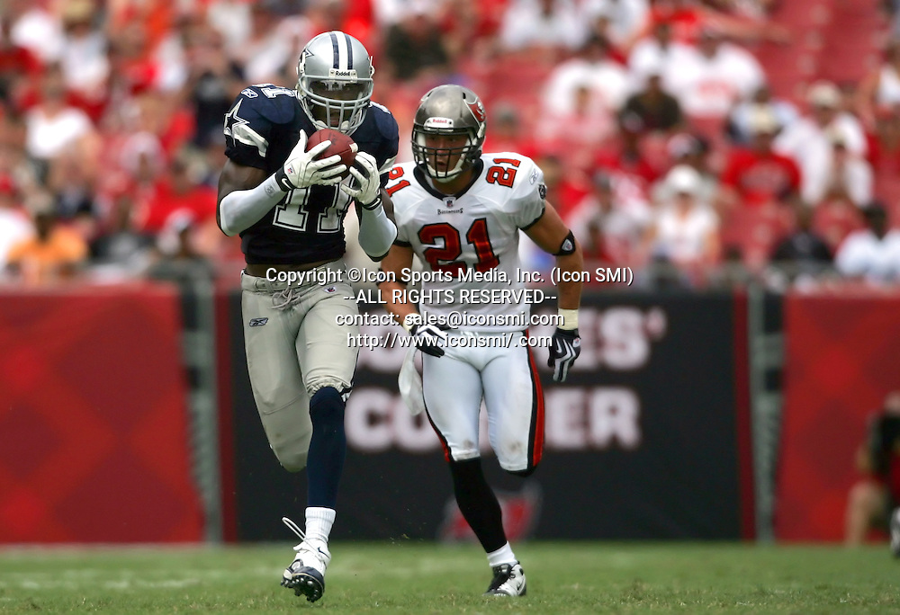 13 SEP 2009: Roy Williams (11) of the Cowboys catches a pass from Tony Romo and goes the distance for a touchdown as Sabby Piscitelli (21) of the Buccaneers looks on during the game between the Dallas Cowboys and the Tampa Bay Buccaneers at Raymond James Stadium in Tampa, Florida.