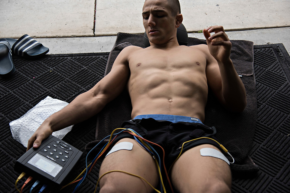 June 7, 2017 / Yorba Linda, Calif.<br /> <br /> Following his workout, 20-30 minutes are spent with pads taped to him stimulating his muscles to aid in blood flow and thus recovery time. Aaron Pico, 20, keeps an eye on the machine that is counting down his time. (Melissa Lyttle for ESPN)