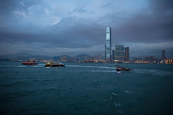 Hong Kong, China skyline lit up against a stormy evening sky viewed across Victoria Harbor with boats on water in foreground.