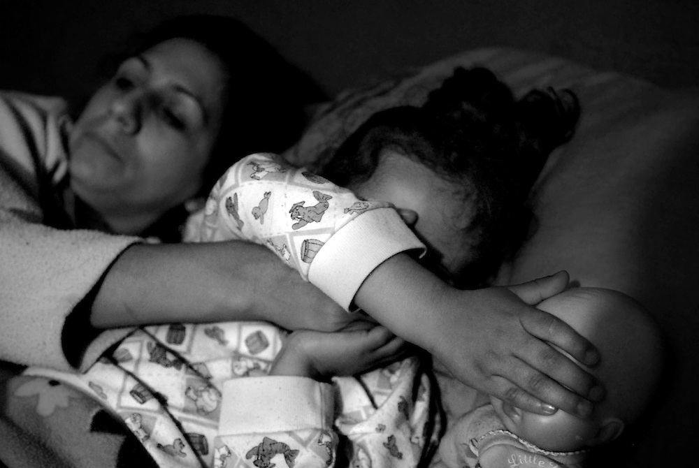 Alejandra Penaloza covers the eyes of her daughter, Samantha, while watching a murder scene on tv.