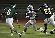 Xavier's Brendan Miller (25) tries to get around Kennedy's Logan Daughetee (6) and Prince Kollie (23) during their game at Kingston Stadium in Cedar Rapids on Friday, September 27, 2013.