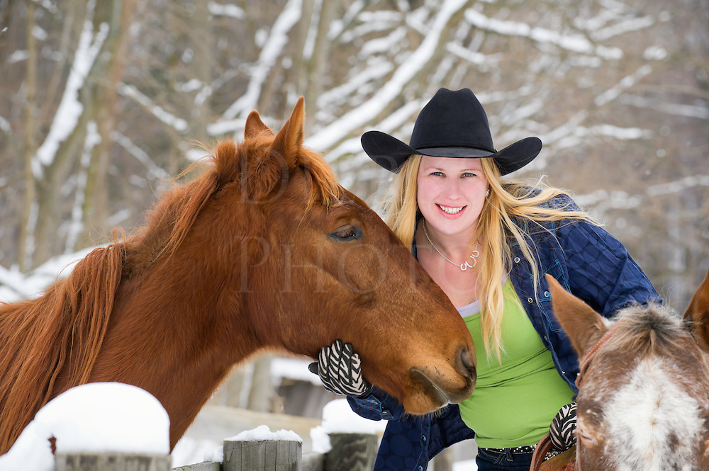 Mounted woman horseback riding visits with a friendly yearling horse over a fence, winter with snow on tree limbs background, happy attractive blonde in western apparel with black cowboy hat, Pennsylvania, PA, USA.