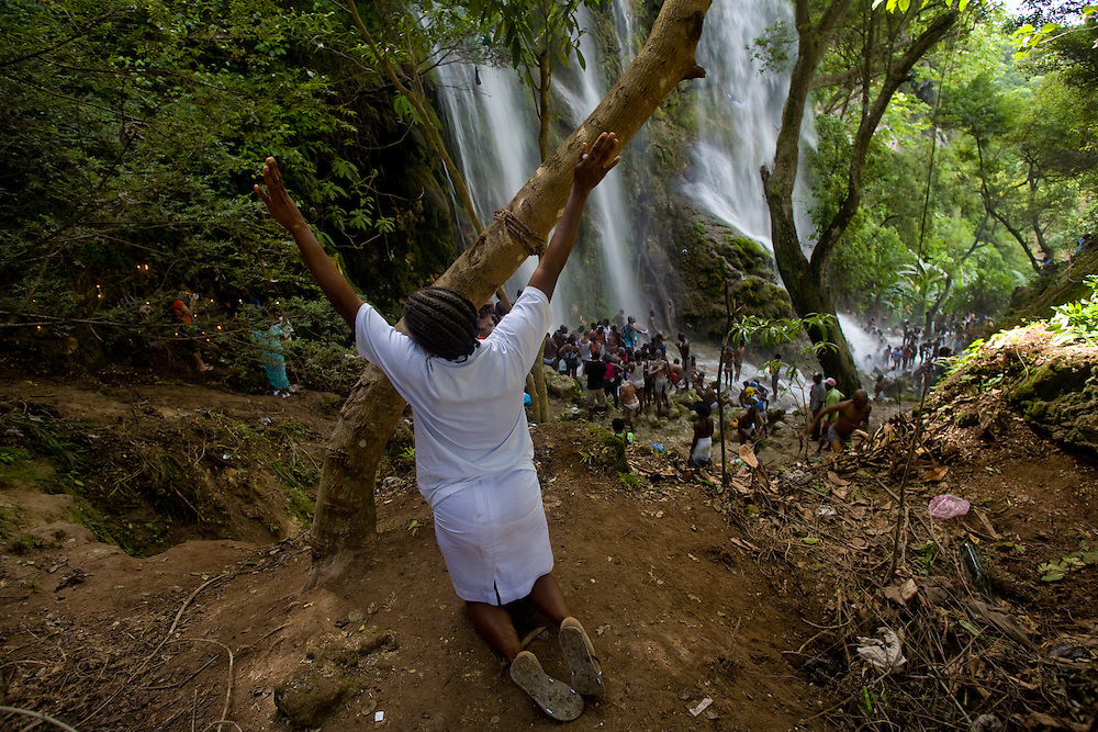 A supplicant prays while other pilgrims bathe in the waterfall at Saut d'Eau on July 16th, the anniversary of the 1983 sighting of the Virgin Mary, alternately identified as the Vodou loa, or spirit, of Erzulie Freda, the Goddess of Love..The waterfall at Saut D'Eau is the site of the largest Vodou and Catholic pilgrimage in Haiti. A second sighting of the Virgin was reported during the American occupation. Each year, thousands of Haitian pilgrims make their way to Saut D'Eau to bathe in the sacred water and revel in the presence of the loa, particularly Erzulie and Damballah the Serpent, father of all life and keeper of spiritual wisdom, who is said to live in the falls. The water is believed to be curative and many women come to Saut d'Eau seeking fertility.