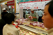 During their expedition to Ito Yokado, a Japanese supermarket chain, the Dongs (Mr. Dong at right) of Beijing, China, inspect fresh meat at the butcher counter. In other ways too, the supermarket hews closely to Western models, right down to the workers offering samples. (Supporting image from the project Hungry Planet: What the World Eats). The Dong family of Beijing, China, is one of the thirty families featured, with a weeks' worth of food, in the book Hungry Planet: What the World Eats.