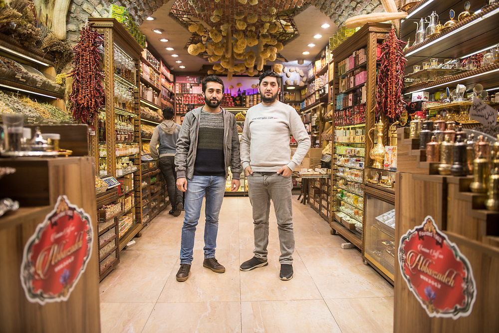 Two adult male merchants pose together for photo in front of spice shop in Istanbul Spice bazaar in Turkey