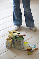 Woman standing by painting materials on floor