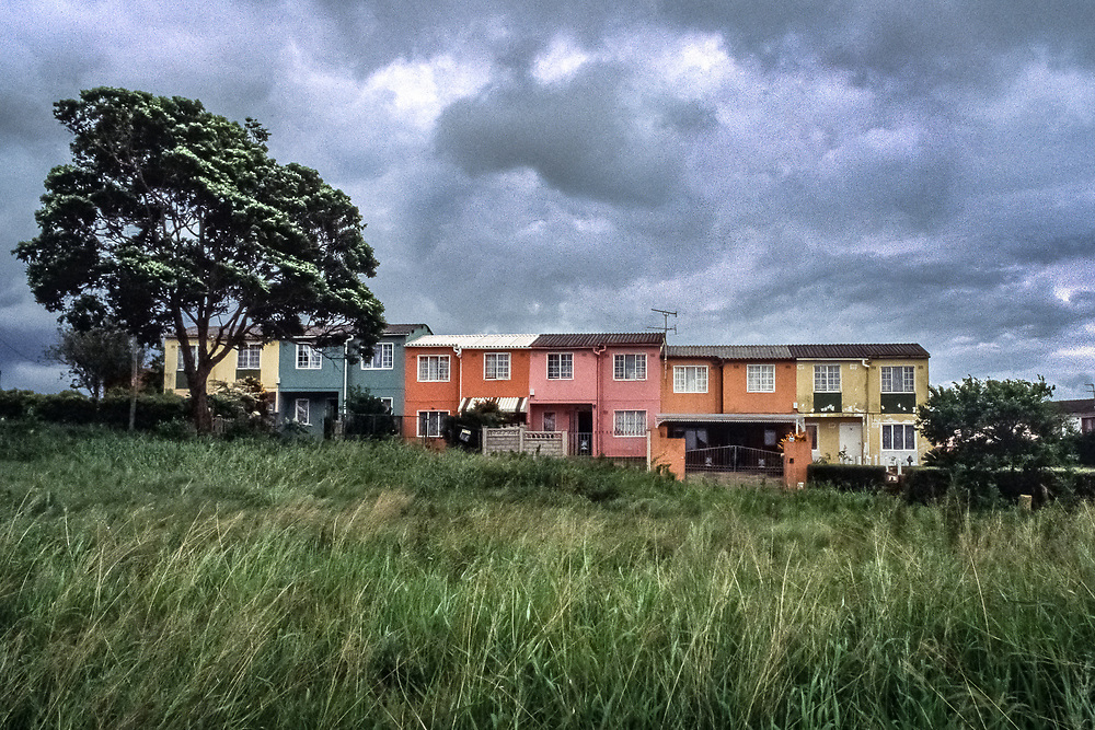 Durban, South Africa: A row of houses in the Indian township of Phoenix, near the settlement where Mohandas K. Gandhi, a London-trained lawyer, established a school, printing press, and newspaper to promote the interests of Indian laborers in the British colony and to develop his philosophy of satyagraha. The area had originally been a sugar estate.