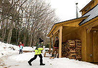 Jacoby Drouin and Brent Howard collects sap while Michael Drouin chops wood at the new sap house at Gilford Elementary School.  (Karen Bobotas/for the Laconia Daily Sun)