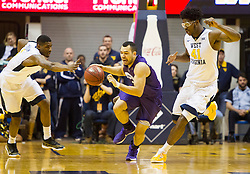 Feb 13, 2016; Morgantown, WV, USA; TCU Horned Frogs guard Michael Williams (2) dribbles between West Virginia Mountaineers defenders during the first half at the WVU Coliseum. Mandatory Credit: Ben Queen-USA TODAY Sports