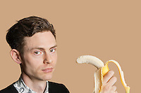 Portrait of a mid adult man holding banana over colored background