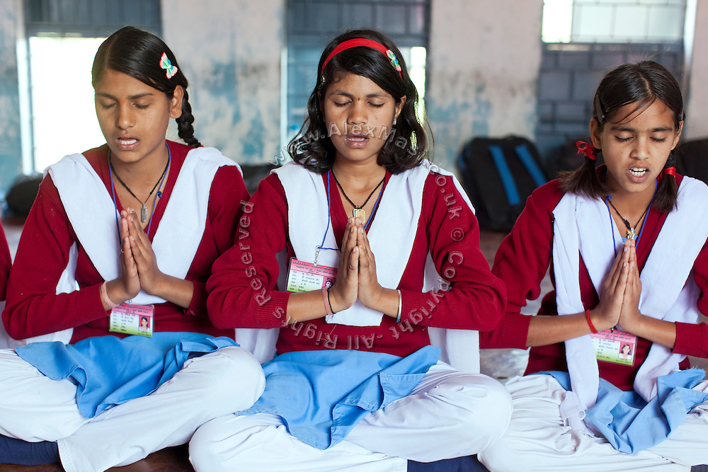Ritu Gaur, 13, (centre) is praying before receiving a meal inside the MS Jamoniya Tank Schhol, near Sehore, Madhya Pradesh, India. Ritu lives in the adjacent Jamoniya Tank Girls Hostel, where the Unicef India Sport For Development Project has started in 2012. Covering 313 state-run girls' hostels and 207 mixed hostels in Madhya Pradesh, the project ensures that children from Scheduled Tribes (ST) and others amongst the poorest people in India, can easily access education and be introduced to sports. Field workers from Unicef also oversee their nutrition and monitor the overall conditions of each pupil.