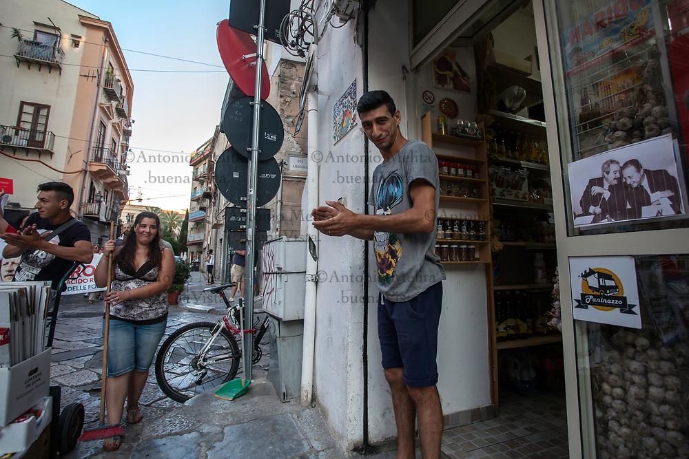 Commerciante applaude al passaggio del corteo delle Agende Rosse. Nella vetrina del suo negozio una celebra foto dei giudici Falcone e Borsellino.