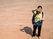 13 MARCH 2013 - ALONG HIGHWAY 13, LAOS: A Chinese migrant worker headed to Laos looks for a ride near the end of Highway 13 in the Boten Special Economic Zone. The SEZ is in Laos immediately south of the Lao Chinese border. It has turned into a Chinese enclave but many of the businesses struggle because their goods are too expensive for local Lao to purchase. Some of the hotels and casinos in the area have been forced to close by the Chinese government after reports of rigged games. The paving of Highway 13 from Vientiane to near the Chinese border has changed the way of life in rural Laos. Villagers near Luang Prabang used to have to take unreliable boats that took three hours round trip to get from the homes to the tourist center of Luang Prabang, now they take a 40 minute round trip bus ride. North of Luang Prabang, paving the highway has been an opportunity for China to use Laos as a transshipping point. Chinese merchandise now goes through Laos to Thailand where it's put on Thai trains and taken to the deep water port east of Bangkok. The Chinese have also expanded their economic empire into Laos. Chinese hotels and businesses are common in northern Laos and in some cities, like Oudomxay, are now up to 40% percent. As the roads are paved, more people move away from their traditional homes in the mountains of Laos and crowd the side of the road living off tourists' and truck drivers.    PHOTO BY JACK KURTZ