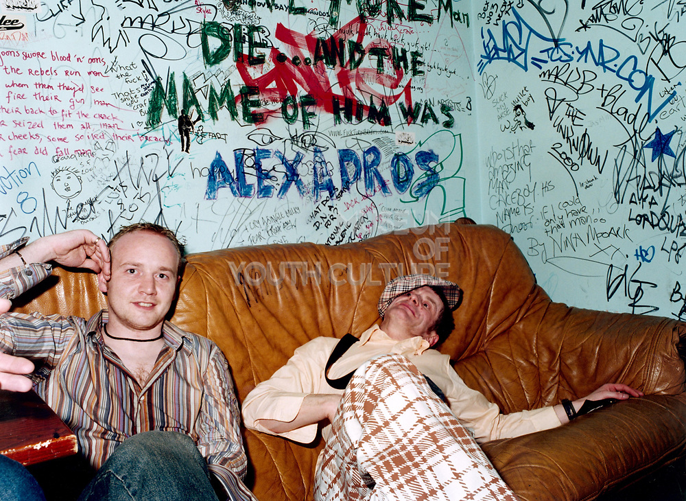 Young man looking at camera smiling sitting next to another young man slouched on couch.