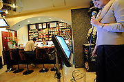 A woman prepares to sing karaoke as Kazuo Tateishi enjoys a bowl of instant noodles at the counter of Instant Noodle Sakura in Tokyo, Japan on 06 November 2008. The pub-cum-eatery boasts a menu of fine wines, cocktails, instant noodles and 10,000 karaoke tunes..