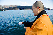 A Buddhist monk casts prayers into the sea in following a ceremony to mark the one year anniversary of last year's magnitude 9 earthquake and tsunamis during a remembrance service in Ofunato City, Iwate Prefecture, Japan on 11 Mar. 2012. .Photographer: Robert Gilhooly