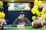 Jason Scempos poses with a duplicate National Letter of Intent to play football at the University of Washington during the NCAA National Signing Day event at Milpitas High School in Milpitas, California, on February 4, 2015. (Stan Olszewski/SOSKIphoto)