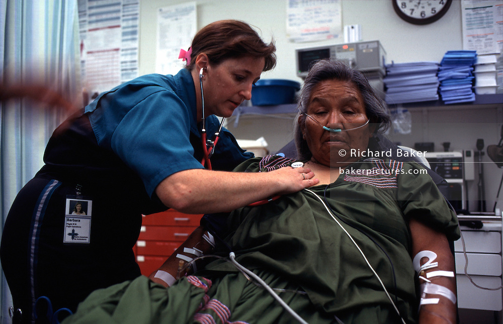 "A flight nurse examines a lady from the Native American Reserve at San Carlos, Arizona, from where she is to be taken from the rural Arizona airstrip by  twin-propeller powered aircraft, an air ambulance, to hospital for treatment. The San Carlos Apache Indian Reservation, in southeastern Arizona, United States, was established in 1872 as a reservation for the Chiricahua Apache tribe. It was referred to by some as ""Hell's Forty Acres,"" due to a myriad of dismal health and environmental conditions. The San Carlos Reservation is one of the poorest Native American communities in the United States, with an annual median household income of approximately $14,000 in 2000, according to the US Census. About 60% of the people live under the poverty line, and 68% of the active labor force is unemployed"