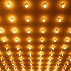 Photo of theater lights in rows on the entrance of a move theater. This type of lighting is commonly referred to as theatre lighting, casino lighting or Broadway lighting. Image is high resolution and is available as a stock photo, poster or print.