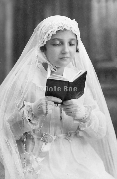 girl posing reading the bible to commemorate her holy communion 1920s