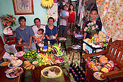 (MODEL RELEASED IMAGE). The Cabaña family in the main room of their 200-square-foot apartment in Manila, the Philippines, with a week's worth of food. Seated are Angelita Cabaña, 51, her husband, Eduardo Cabaña, 56 (holding sleeping grandson Dave, 2), and their son Charles, 20. Eduardo, Jr., 22 (called Nyok), his wife Abigail, 22, and their daughter Alexandra, 3, stand in the kitchen. Behind the flowers is the youngest son, Christian, 13 (called Ian). The Cabaña family is one of the thirty families featured in the book Hungry Planet: What the World Eats (p. 234).