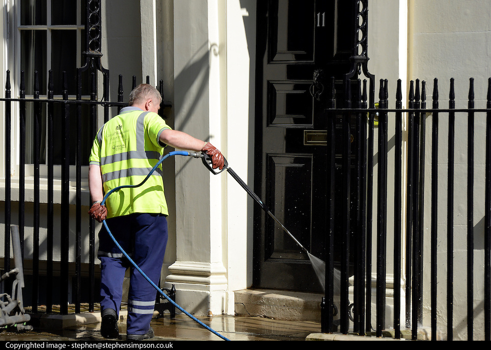 © Licensed to London News Pictures. 30/05/2012. London, UK A workman cleans the steps of number eleven Downing Street with a powerful hose connected to a street cleaning vehicle. Preparations today 20th May 2012 around London ahead of The Queen's Diamond Jubilee this weekend. Photo credit : Stephen Simpson/LNP