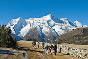 Sagarmatha National Park, Nepal: Nepalese people walk above the village of Namche Bazaar, about 4 kilometers from the snowy mountain of Kongde Ri (sometimes called Kwangde Ri; 20,320 feet elevation) in the Himalaya of eastern Nepal. Sagarmatha National Park was created in 1976 and honored as a UNESCO World Heritage Site in 1979.