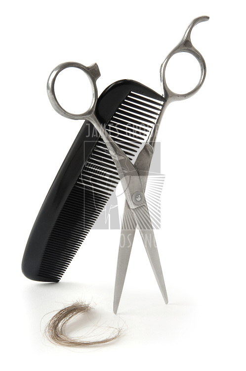 Scissors and comb with a lock of hair on a white background