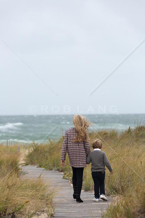little girl and boy walking on a beach walkway towards the ocean in the Winter