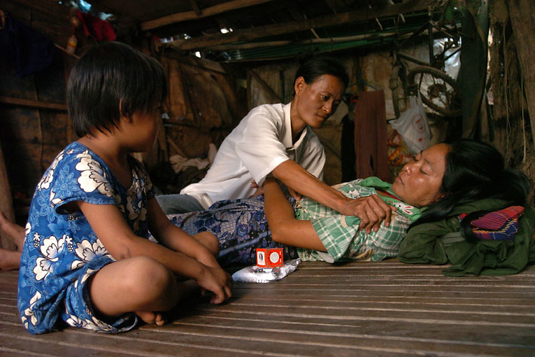 Cambodia. Phnom Penh. 2006. Hen, an outreach worker living with HIV, and formerly a sex worker, messages Yok Ourn, a sex worker suffering from HIV during a home based care visit. Hen is working with Chhouk Sar; a small NGO run by former and current sex workers. Outreach workers use the Karnofsky scale to assess the health of the patients, take turns to care for her if she does not have anybody else, and provide food when required. Outreach workers also negotiate with local hospitals to ensure sick sex workers have equitable access to such services.