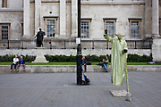Street busker dressed as Star Wars character Yoda with tourists in Trafalgar Suare.