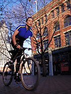 Lifestyle image of young female athlete riding a bike through Pioneer Square in Seattle, WA.