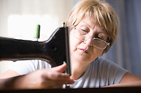 Mature woman adjusts foot of sewing machine