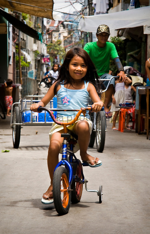 MANILA (Philippines). 2009. a child learning to ride a bicycle on the streets of Manila.