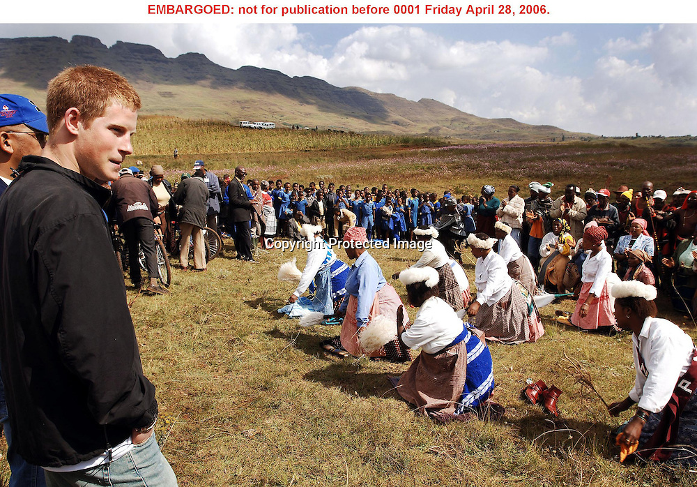 Prince Harry watches a group of women singing in the village of Phororong high in the Northern Mountains, while on a return visit to Lesotho in Southern Africa onTuesday April 25 2006. The Prince was in the country to launch his new charity called 'Sentebale', which means 'forget me not' in memory of his mother Diana Princess of Wales. <br />