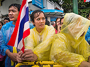 05 MAY 2013 - BANGKOK, THAILAND:  A Thai woman holds the Thai flag while she waits to see Bhumibol Adulyadej, the King of Thailand, Sunday. The King and Queen, who are both hospitalized and in poor health, did not attend Sunday's event. May 5 marks the 63rd anniversary of the Coronation of His Majesty King Bhumibol Adulyadej. The day is celebrated as a national holiday; since this year it falls on a Sunday, it will be observed on Monday May 6, and as such all government offices and commercial banks will close for the day. HM King Bhumibol Adulyadej is the longest reigning monarch in the world. Each year on the 5th of May, the Kingdom of Thailand commemorates the day when, in 1950, the Coronation Ceremony was held for His Majesty King Bhumibol Adulyadej, the 9th in the Chakri Dynasty (Rama IX). On the 5th of May, His Majesty conducts a merit making ceremony, presenting offerings to Buddhist monks, and leads a ?Wien Thien? ceremony, walking three times around sacred grounds at the Temple of the Emerald Buddha.    PHOTO BY JACK KURTZ