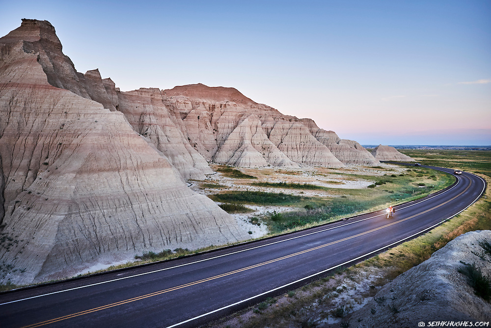 A motorcycle tours on the highway tours scenic Badlands National Park, South Dakota