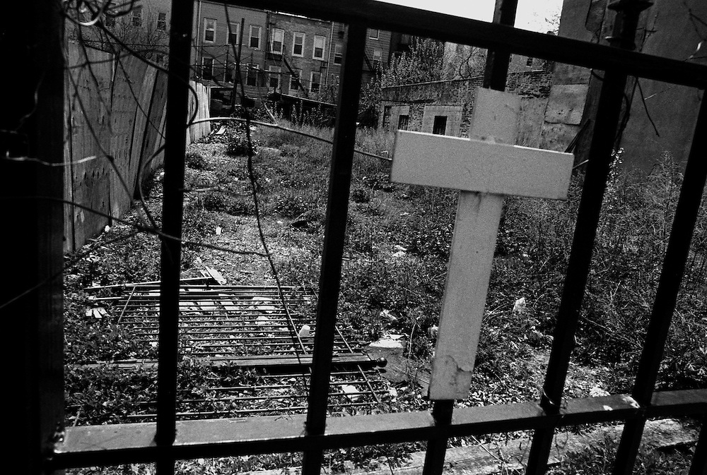 """Cross on a fence near a church in the Bedford-Stuyvessant neighborhood of Brooklyn...Part of long-term (2005-2008) story """"I See A Darkness"""". New York, NY."""