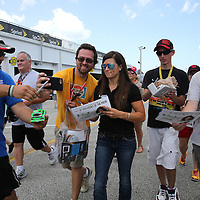 Sprint Cup Series driver Danica Patrick (10) signs autographs as she walks down pit lane during the 57th Annual NASCAR Coke Zero 400 race first practice session at Daytona International Speedway on Friday, July 3, 2015 in Daytona Beach, Florida.  (AP Photo/Alex Menendez)