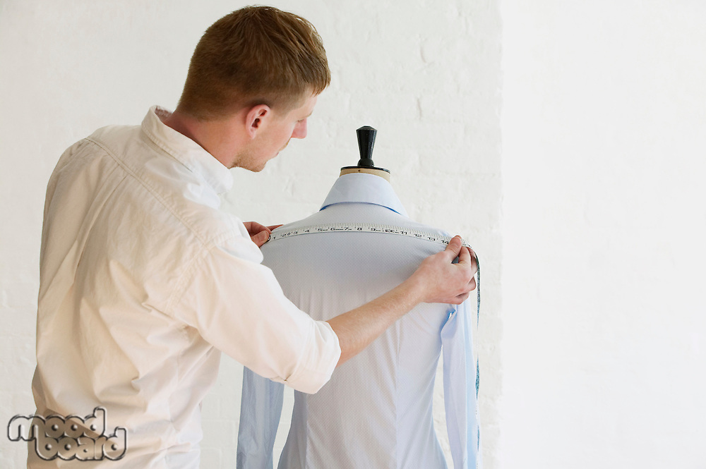 Tailor measuring blouse hanging on mannequin back view