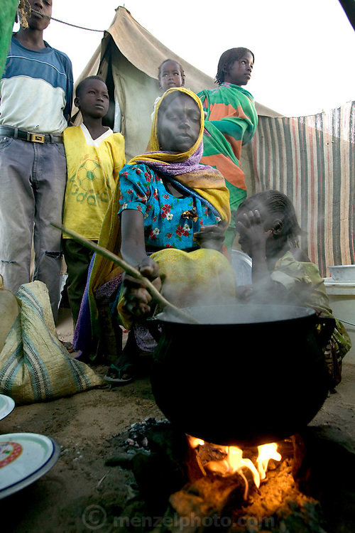 (MODEL RELEASED IMAGE). Squatting before the fire with her children, Sudanese Refugee D'jimia Ishakh Souleymane stirs a pot of aiysh, the thick porridge that this refugee family eats three times a day. Despite losing almost everything in their flight from militia attacks, D'jimia keeps her improvised household as orderly as possible. To cover the ground inside, the family hauled in clean sand from the dry riverbed. D'jimia and the children sleep on two blankets, which she constantly airs out and washes. (Supporting image from the project Hungry Planet: What the World Eats.)