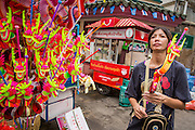 17 OCTOBER 2012 - BANGKOK, THAILAND:    A toy vendor during the Vegetarian Festival on Yaowarat Road in Bangkok's Chinatown. The Vegetarian Festival is celebrated throughout Thailand. It is the Thai version of the The Nine Emperor Gods Festival, a nine-day Taoist celebration celebrated in the 9th lunar month of the Chinese calendar. For nine days, those who are participating in the festival dress all in white and abstain from eating meat, poultry, seafood, and dairy products. Vendors and proprietors of restaurants indicate that vegetarian food is for sale at their establishments by putting a yellow flag out with Thai characters for meatless written on it in red.       PHOTO BY JACK KURTZ