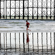 .A boy plays on the shore line of Brighton beach yesterday as the tide goes out next to the West Pier. <br />