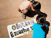 05 OCTOBER 2013 - PHOENIX, ARIZONA: Girls write a sign calling for President Obama to listen to immigrants during an immigration reform rally in Phoenix. Escucha is Spanish for listen. More than 1,000 people marched through downtown Phoenix Saturday to demonstrate for the DREAM Act and immigration reform. It was a part of the National Day of Dignity and Respect organized by the Action Network.  PHOTO BY JACK KURTZ