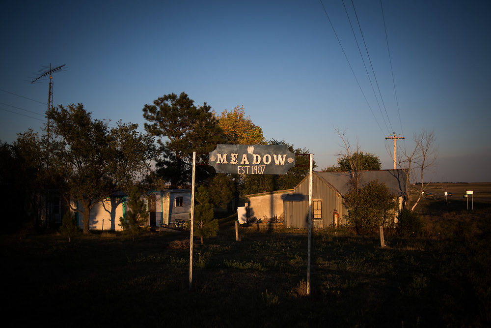 A handmade sign for Meadow, SD is lit by a sunset on October 6, 2017. The town has only 5 people living on main street but still maintains a post office and one of the most popular bars in the area.