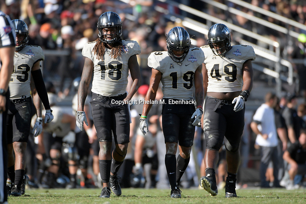 Central Florida linebacker Shaquem Griffin (18), defensive back Mike Hughes (19) and defensive lineman Seyvon Lowry (49) walk onto the field during the second half of the American Athletic Conference championship NCAA college football game against Memphis Saturday, Dec. 2, 2017, in Orlando, Fla. Central Florida won 62-55. (Photo by Phelan M. Ebenhack)